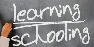 Learning and schooling written on a chalkboard