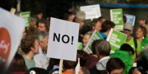 """Protester carrying a sign that reads """"no"""""""